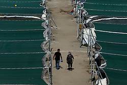 October 5, 2016 - Athens, Greece - Migrants walk among UNHCR tents set in a sports facility at Helliniko Olympic complex south suburb of Athens, Greece on October 5, 2016.  Almost 2,500 migrants and refugees, mainly Afghani, are housed at the former Athens airport site, an olympic complex used in the 2004 Olympics. In total 60.736 refugees and other migrants are stranded in Greece. ..Almost 2,500 migrants and refugees, mainly Afghani, are housed at the former Athens airport site, and to an olympic complex used in the 2004 Olympics. In total 60.736 refugees and other migrants are stranded in Greece. (Credit Image: © Panayiotis Tzamaros/NurPhoto via ZUMA Press)