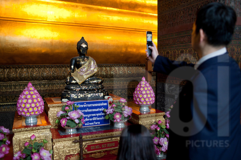 A man in a suit photographs a Buddha statue, Bangkok, Thailand, Southeast Asia