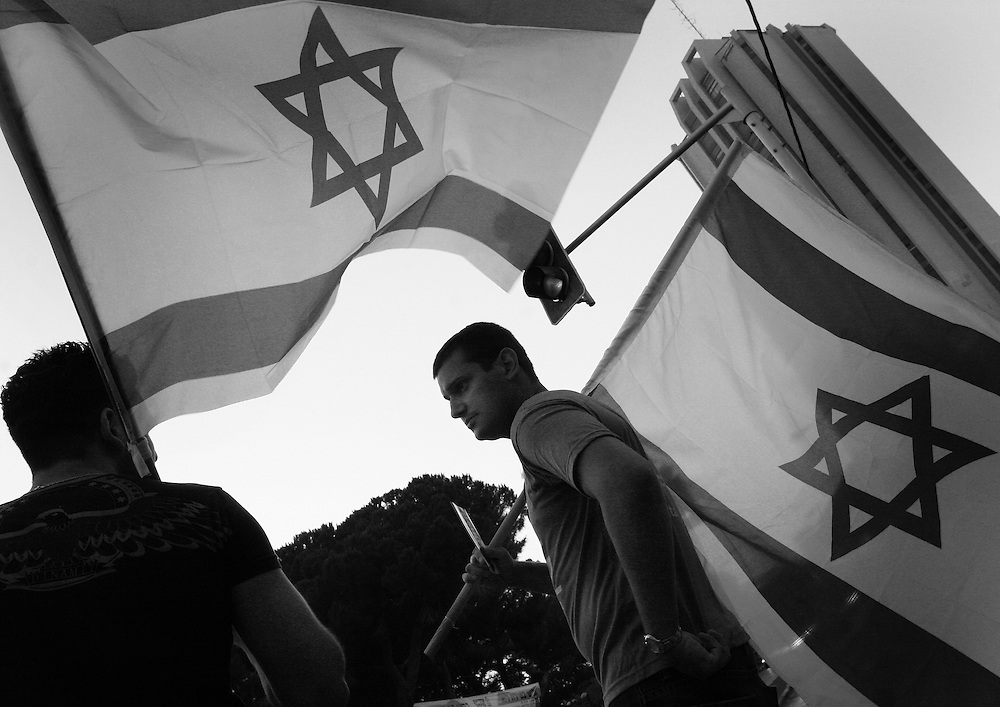 Two young men with Israeli flags in Haifa showing their support for the war going on in the north of the country with Hezbollah.