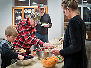 """26 FEBRUARY 2020 - FARMINGTON, MINNESOTA: NICHOLAS FRIEDGES gets a salad at the community dinner at Faith Church, a United Methodist Church in Farmington, MN, about 30 minutes south of the Twin Cities. The dinner is sponsored by Loaves & Fishes, a Christian organization that provides food for community dinners and foodbanks. Farmington, with a population of 21,000, is a farming community that has become a Twin Cities suburb. The city lost its only grocery store, a Family Fresh Market, in December, 2019. The closing turned the town into a """"food desert."""" In January, Faith Church started serving the weekly meals as a response to the store's closing. About 125 people per week attend the meal at the church, which is just a few blocks from the closed grocery store. The USDA defines food deserts as having at least 33% or 500 people of a census tract's population in an urban area living 1 mile from a large grocery store or supermarket. Grocery chains Hy-Vee and Aldi both own land in Farmington but they have not said when they plan to build or open stores in the town.       PHOTO BY JACK KURTZ"""