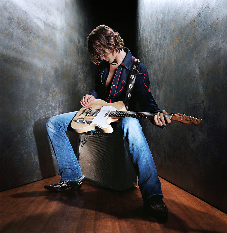 Musician sitting on old fender amp and playing a old fender telecaster guitar.