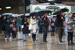 © Licensed to London News Pictures. 28/03/2018. London, UK. Commuters wait for a bus at Waterloo Station during rain and wet weather this morning. Photo credit: Vickie Flores/LNP
