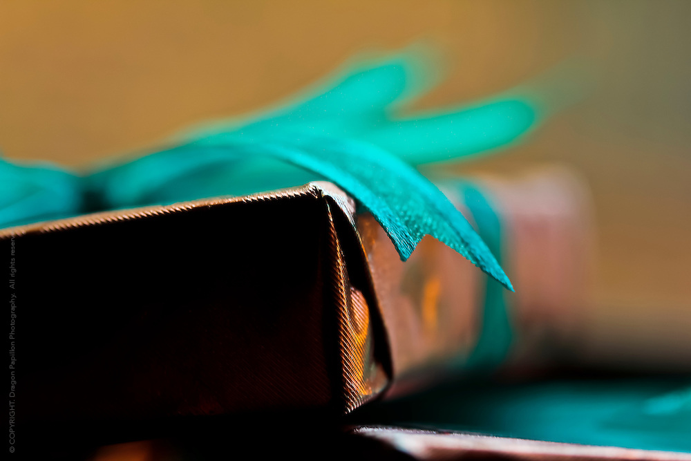 closeup of corner of gift wrapped in bronze paper with end of teal bow showing in detail