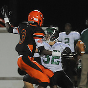 West Brunswick's Hunter Chaney looks to throw under cover by New Hanover's Deonte Adger Friday October 24, 2014. (Jason A. Frizzelle)