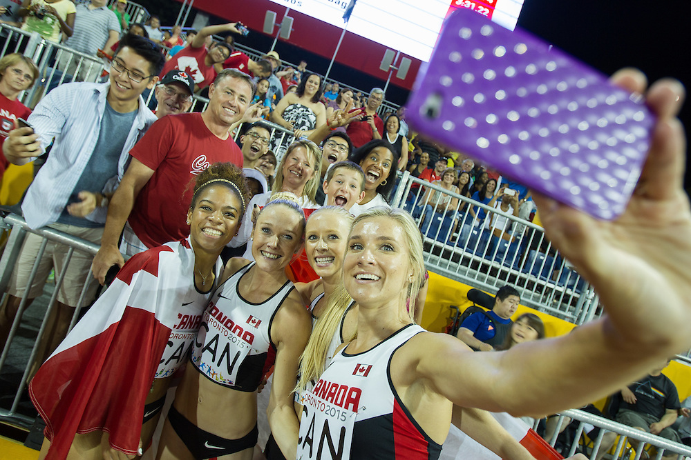 Canada's 4X400 team of (L-R) Taylor Sharpe, Sarah Wells, Sage Watson and Brianne Theisen-Eaton take a selfie as they celebrate their bronze medal win at the 2015 Pan American Games at CIBC Athletics Stadium in Toronto, Canada, July 25,  2015.  AFP PHOTO/GEOFF ROBINS