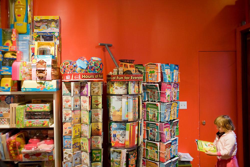 """7 Novembre, 2008. Brooklyn, New York.<br /> <br /> Una bambina sceglie un libro al Lulu's Cuts & Toys, una parruccheria per bambini e negozio di giocattoli a Park Slope, Brooklyn, NY. Park Slope, spesso definito dai newyorkesi come """"The Slope"""", è un quartiere nella zona ovest di Brooklyn, New York, e confinante con Prospect Park.  Park Slope è un quartiere benestante che ha il maggior numero di nascite, la qualità della vita più alta e principalmente abitato da una classe media di razza bianca. Per questi motivi molte giovani coppie e famiglie decidono di trasferirsi dalle altre municipalità di New York a Park Slope. Dal punto di vista architettonico, il quartiere è caratterizzato dai brownstones, un tipo di costruzione molto frequente a New York, e da Prospect Park.<br /> <br /> ©2008 Gianni Cipriano for The New York Times<br /> cell. +1 646 465 2168 (USA)<br /> cell. +1 328 567 7923 (Italy)<br /> gianni@giannicipriano.com<br /> www.giannicipriano.com"""