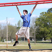 Lauren Wood | Buy at photos.djournal.com<br /> Dayton Palmer, 16, demonstrate an around the world exercise on the monkey bars during a Project Fit America assembly Friday afternoon at Hills Chapel School in Booneville.