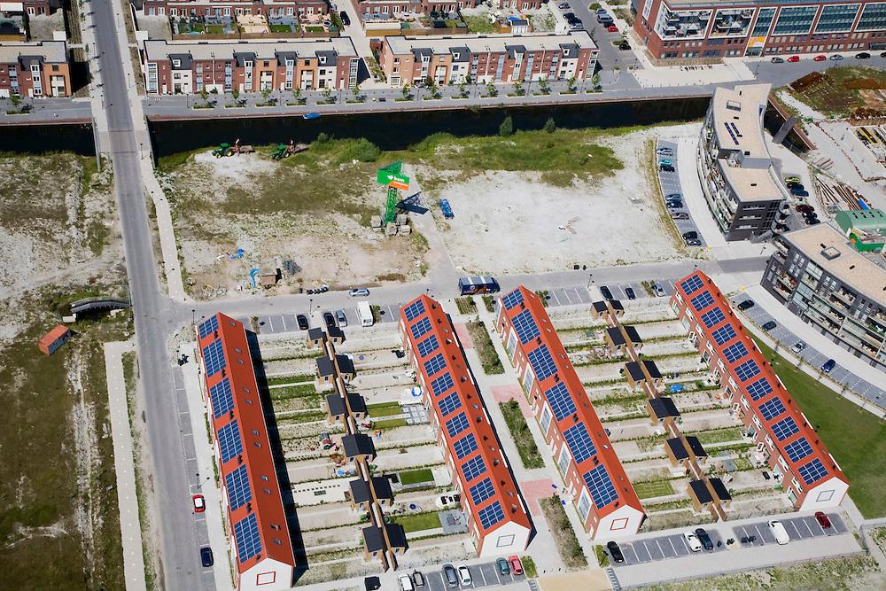 Nederland, Noord-Holland, Heerhugowaard, 14-07-2008; rijtjeshuizen met schuurtjes en tuintjes, zojuist opgeleverd in Stad van de Zon (Sun City), geesteskind van Ashok Bhalotra; nieuwbouwwijk op VINEX lokatie, in de Polder Heerhugowaard tussen de dorpskern Heerhugowaard en Alkmaar; milieuvriendelijke wijk, energiezuinige huizen die bovendien uitgerust zijn met zonne-energie panelen, zonnepanelen, zonne-energie panelen, zonnepaneel, paneel, schuur, tuin, gezin, huisje boompje beestje; Sun City, new housing estate in Northwest of the Netherlands, energy neutral - environmetal friendly houses, equiped with individual solar panels; suncity;  solar energy, solar panel, solar power. .luchtfoto (toeslag); aerial photo (additional fee required); .foto Siebe Swart / photo Siebe Swart