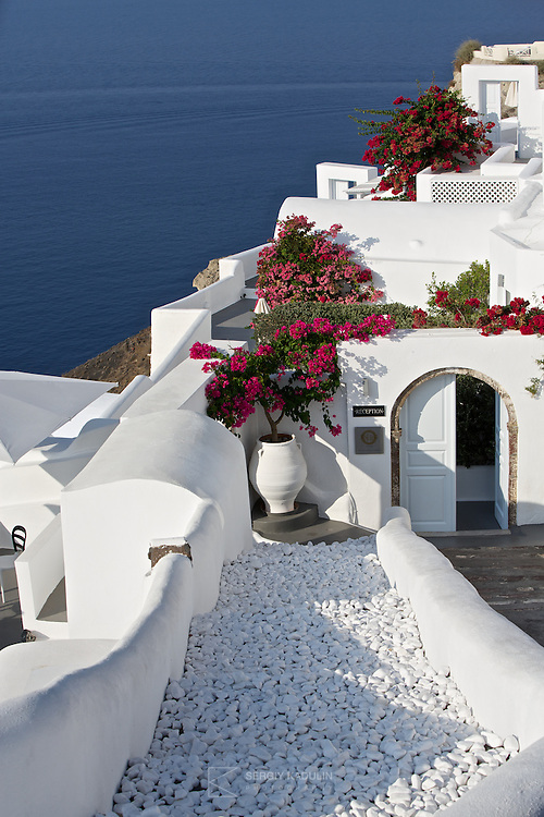 Residential and hotel area in Oia village on Santorini island, Greece. Morning sunlight exterior view with white houses in the foreground and blue sea in the back.