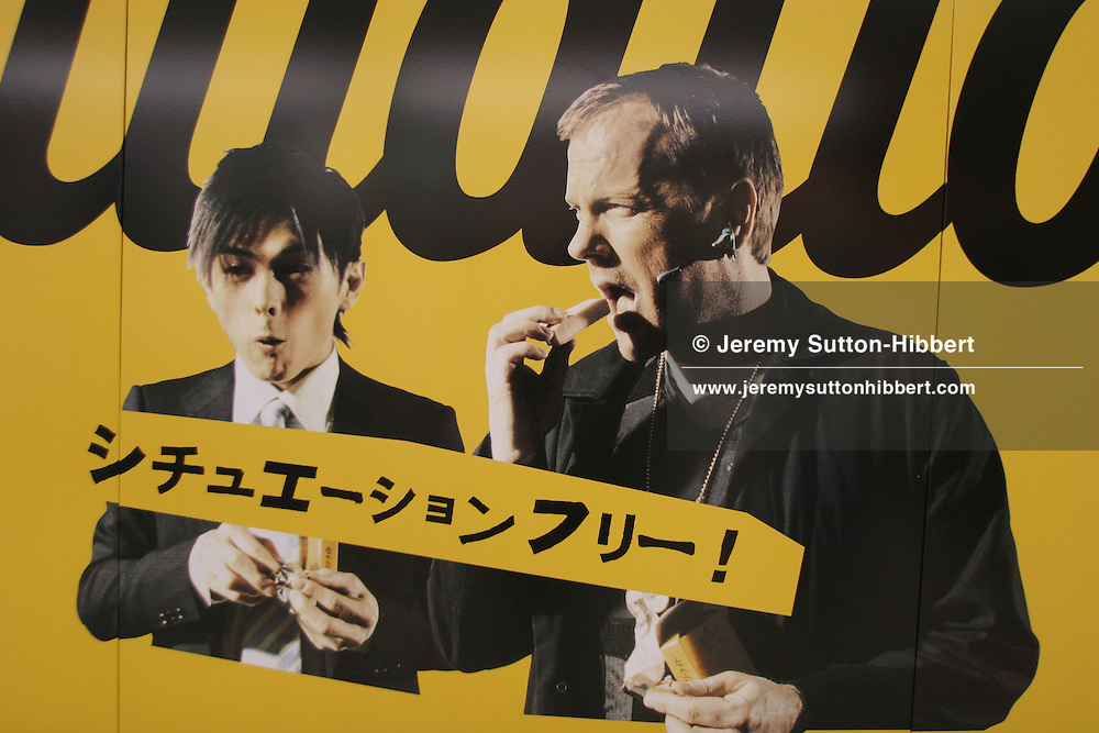 "KIEFER SUTHERLAND IN BISCUIT ADVERTISEMENT, TOKYO, JAPAN. A Japanese woman in kimono walks past a poster in the underground station depicting American actor, and star of '24', Kiefer Sutherland, advertising 'Calorie Mate' -a Japanese nutritional biscuit snack bar, in Tokyo, Japan, Monday, Oct. 9, 2006.  The Japanese text on the poster reads ""Situation free"", implying the snack bar can be eaten anywhere, anytime, any situation."