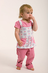 Little girl in the studio with her finger in her mouth,