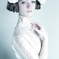 Female youth with fresh skin and clear blue eyes and blonde hair with roses in her hair wearing lace clothes