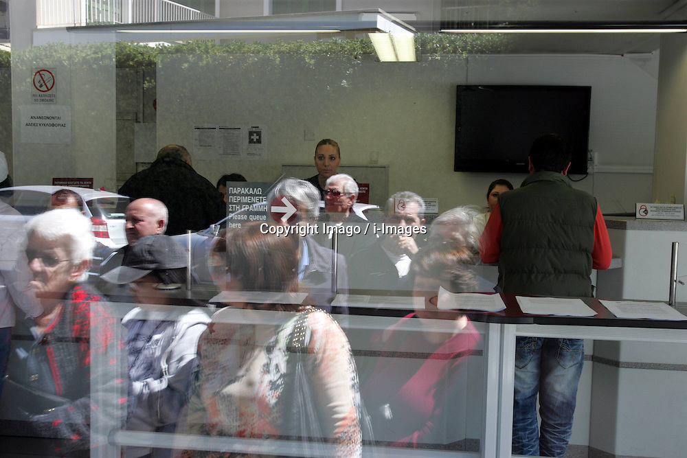 People seen at a branch of Laiki Bank before the reopening of the bank in Nicosia, capital of Cyprus, on March 28, 2013. Surprisingly few lined up outside banks in Cyprus when they reopened for business at noon on Thursday -- to the relief of authorities which have feared a run on the banks following a closure since March 16. Strict limits on bank transactions have been announced by the Central Bank and the ministry of finance in a bid to prevent a massive outflow of cash. A Central Bank official said banks would be open for transactions between 12:00 noon and 18:00 local time (10:00 GMT and 16:00 GMT), instead of the normal 08:30 to 13:00 local time bank hours. The decree imposing controls on bank transaction limits cash withdrawal to 300 euros per day per bank account and entirely prohibits payment by check. However, credit card holders can use them for commercial transactions for unlimited amounts of money., Nicosia, Cyprus, March 28, 2013. Photo by Imago / i-Images...UK ONLY.