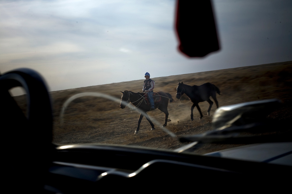 CREDIT: DOMINIC BRACCO II..SLUG:PRJ/KAZAKHSTAN..DATE:10/30/09..CAPTION:On the road to the Dike Kokaral a man takes his horses October 30, 2009 near Aralsk, Kazakhstan. The Dike Kokaral was completed in 2005 to help combat the Aral Sea's diminishing waters...Aral Sea Overview: ..During the 1960s the USSR began irrigating the waters of the Aral Sea in southern Kazakhstan to combat their growing food crisis. The Soviets severely miscalculated and water began receding quickly from the port cities. The waters continued to recede. By 2000 the water was 80 km away from the city of Aralsk, a main seaport in Kazakhstan. In 2005 with help from the World Bank, construction began on a 13km dike that locals hoped would bring the waters back to their original shores. The project raised water quality and fishing was able to resume, however four years after completion of the dike the water is still 50km from Aralsk's port. Locals seem mixed on the possibility of the sea returning after more than 40 years without the sea. Fishermen from Aralsk make a three-hour path through soft desert road along the former seabed. The only source of income for many is cattle, horses, and camels, which have, began to overgraze the areas of the former seabed and surrounding desert. Because of this nutrient rich topsoil is lifted by the wind and the process of desertification continues.  .