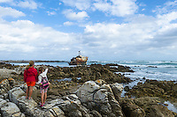 Two children stop to look at a ship wreck that lies against the rugged Agulhas coastline and within the Agulhas National Park. This lies along the Rusperspunt Hiking Trail. Agulhas National Park, Western Cape, South Africa
