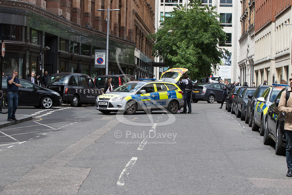Knightsbridge, London, May 19th 2017. A man is arrested near the Ecuadorian embassy in Knightsbridge as the press gather outside following news that Wikileaks founder Julian Assange has had rape charges against him dropped by Swedish prosecutors. The arrest follows a brief episode where a suspicious package was investigated by police, but it is uncertain whether the arrest was connected. PICTURED: A Police vehicle closes Hans Crescent as officers investigate a suspicious package.
