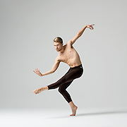 Contemporary male ballet dancer, Andrew Hellerick, in the photo studio on a gray background. Photograph taken in New York City by photographer Rachel Neville.