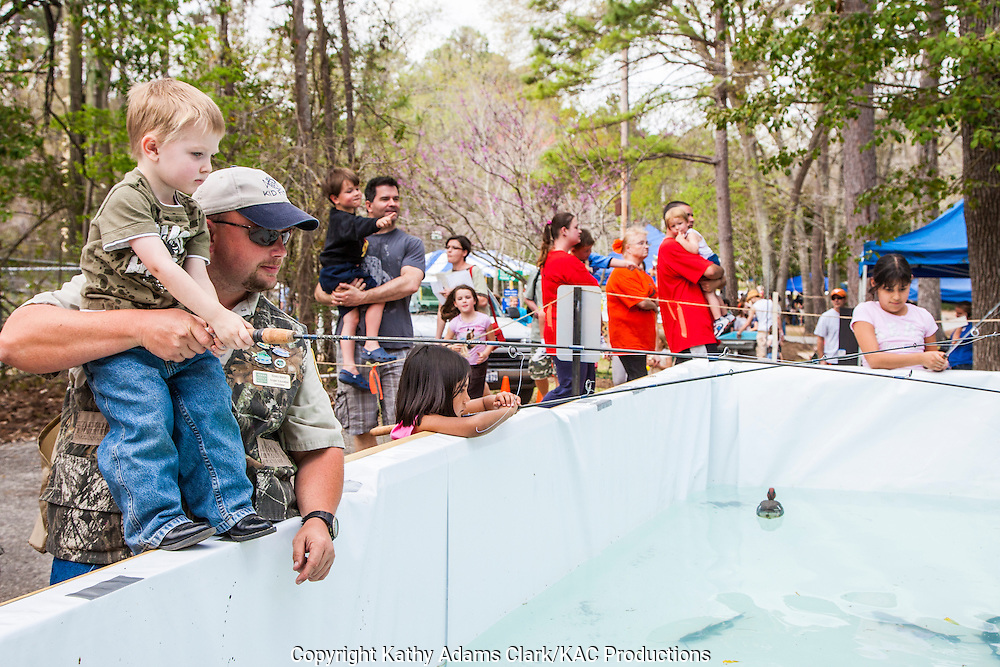 Assisted by Bobby Martin, Angler Education Volunteer, kids enjoy fishing for live fish at the NatureFest at Jones County Park and Nature Center in Humble, Texas, north of Houston.