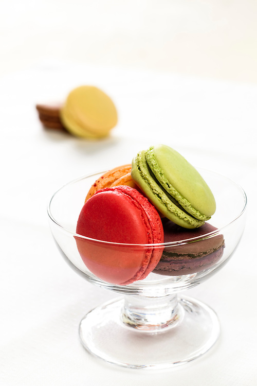 Colorful french pastries in a glass bowl.
