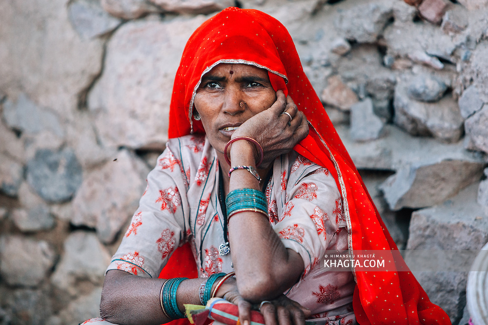 Portrait of an ethnic Rajasthani woman with a bright red veil waits for her turn to collect water from the public well in their village in Rajasthan