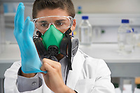 Scientist wearing a gas mask putting on rubber gloves in laboratory