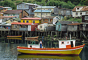 Fishermen's traditional wood houses (palafitos) rise on stilts in Castro on Chiloé Island, in Los Lagos Region, Zona Austral, Chile, South America. Colorful boats are moored on the sea water below. A boy with an arm in a sling stands on a boat painted bright yellow and orange. Founded in 1576, Castro is the capital of Chiloé Province. Isla de Chiloé is the largest island in Chile.