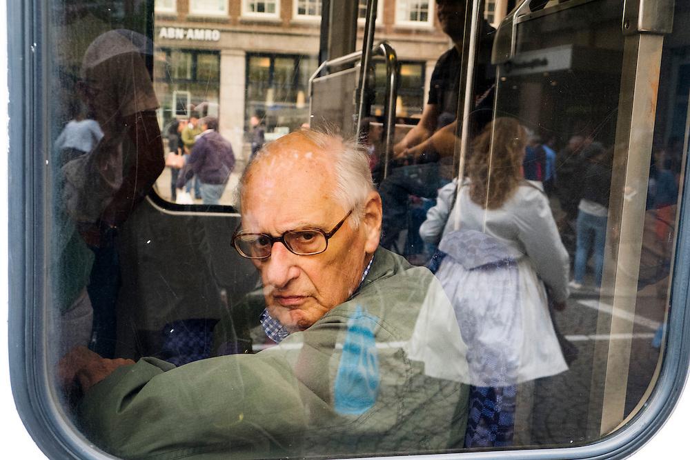 Nederland, Amsterdam, 21 sept 2013<br /> Man in tram staart naar buiten. In de reflectie loopt een dame met wapperende jas, de man kijkt ernaar.<br /> <br />  Foto(c): Michiel Wijnbergh