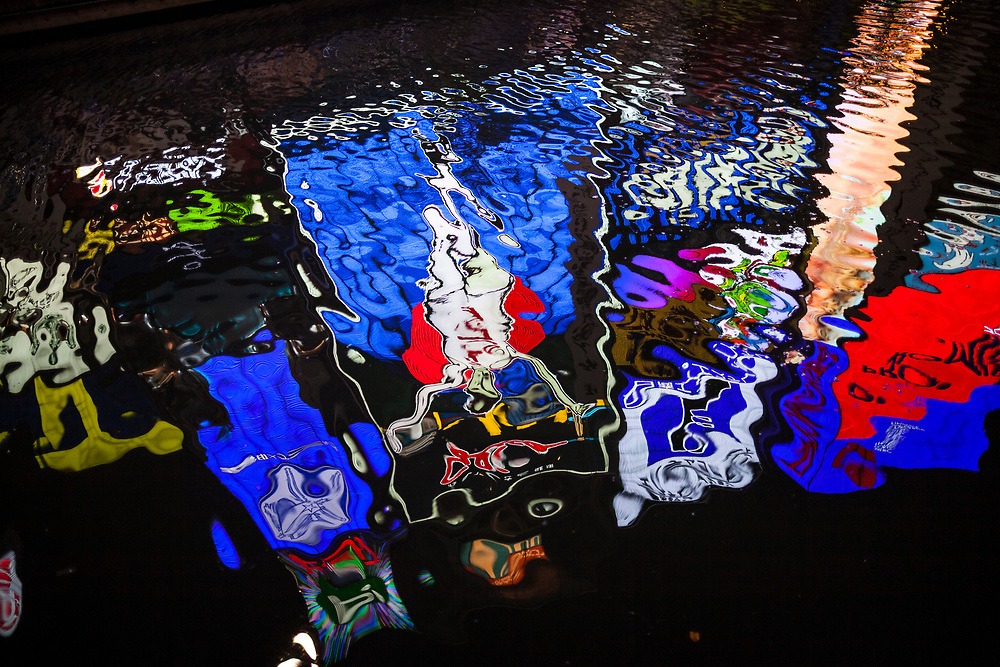 The famous running man neon sign reflected in the water at night along the Dotonbori river in Osaka, Japan.