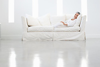 Middle-aged woman relaxing on sofa