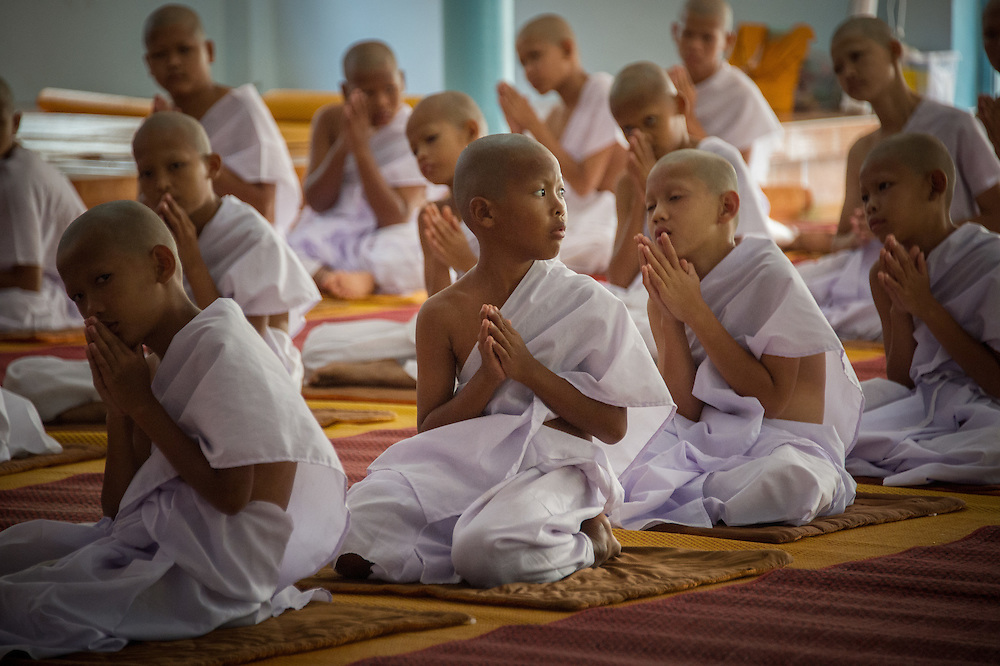 Young men pray at a ceremony to become novice monks in  Rural Nakhon Nayok, Thailand.