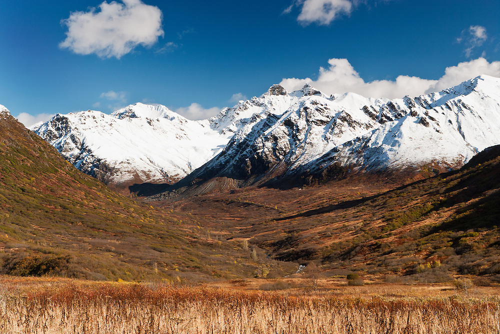 First snow blankets the Talkeetna mountains and contrasts with the fall colors in Hatcher Pass in Southcentral Alaska. Fall. Afternoon.