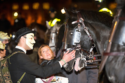 © Licensed to London News Pictures. 05/11/2015. London, UK. A demonstrator stokes the nose of a police horse during An anti-capitalist  protest organised by the group Anonymous outside Parliament in Westminster on bonfire night 05, November 2015. Bonfire night, also known as Guy Fawkes night, is an annual commemoration of when Guy Fawkes, a member of the Gunpowder Plot, was arrested for attempting to blow up the House of Lords at parliament.   Photo credit: Ben Cawthra/LNP