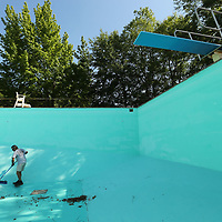 Shawn Roberts sweeps up all the debis off the bottom of the pool at C.C. Agustus before he can finish painting it Tuesday morning so they can get it ready for the summer.