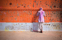 Man prays against red wall with hindu counterclockwise swastika symbols during the kumbh mela festival in india