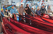 Men pulling red fishing nets at the fishing harbour at M'diq or Rincon, M'diq-Fnideq, on the Mediterranean coast of Morocco. M'diq has 2 harbours, one for tourism and the other for its traditional industry of fishing. Picture by Manuel Cohen