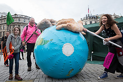 London, UK. 8 October, 2019. Climate activists from Extinction Rebellion mime greedy hands trying to seize the world's resources in Trafalgar Square on the second day of International Rebellion protests to demand a government declaration of a climate and ecological emergency, a commitment to halting biodiversity loss and net zero carbon emissions by 2025 and for the government to create and be led by the decisions of a Citizens' Assembly on climate and ecological justice.