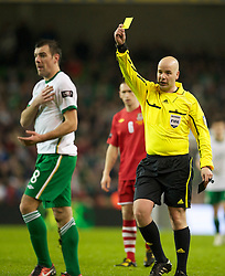 DUBLIN, IRELAND - Tuesday, February 8, 2011: Referee Mark Courtney (Northern Ireland) shows the Republic of Ireland's Darron Gibson a yellow card during the opening Carling Nations Cup match against Wales at the Aviva Stadium (Lansdowne Road). (Photo by David Rawcliffe/Propaganda)