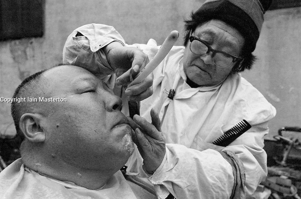 Man having a shave from traveling barber in an old Beijing hutong