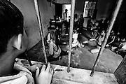 A young woman dance teacher teaches children traditional Cambodian dance called Apsara dance.