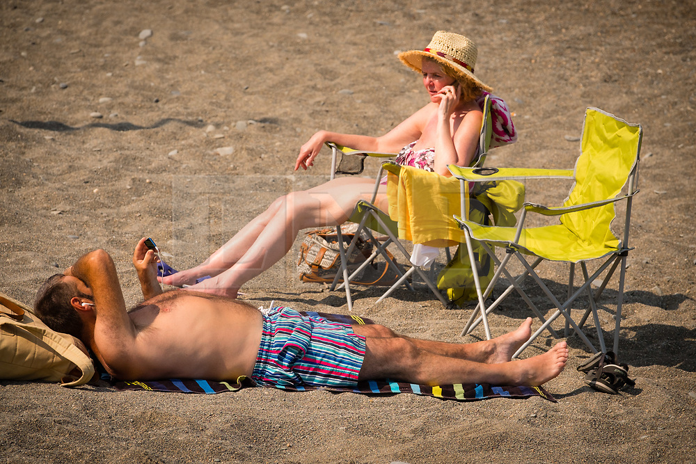 © Licensed to London News Pictures. 05/07/2018. Aberystwyth, UK.  A couple relax on the beach at mid-morning in Aberystwyth at the start of what promises to be yet another hot and almost cloudless day, as the prolonged heatwave continues to dominate the weather over the UK. Photo creditKeith Morris/LNP