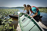 JEROME A. POLLOS/Press..Michael Berntsen, foreground, and Jonathan Flack, a volunteer for a Special Needs Recreation-event held at Hauser Lake, empties water out of a canoe after it capsized Monday.