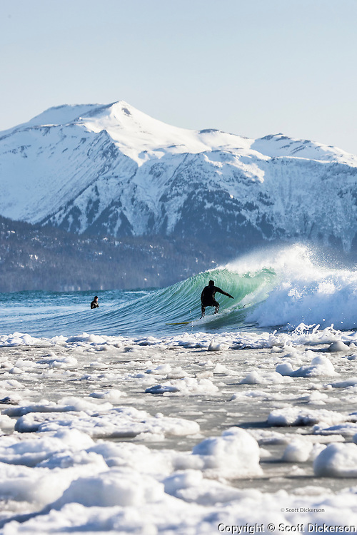 Alaskan surfer Mike McCune rides a wave with snow, slush, and ice packed against the beach during a cold winter surf session in Homer, Alaska. The snowy Kenai mountain range rises from Kachemak Bay in the background.