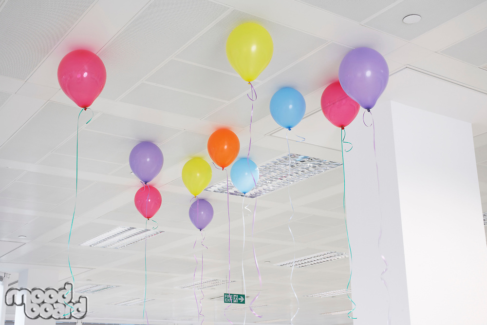 Party balloons hanging from ceiling of empty office space low angle view