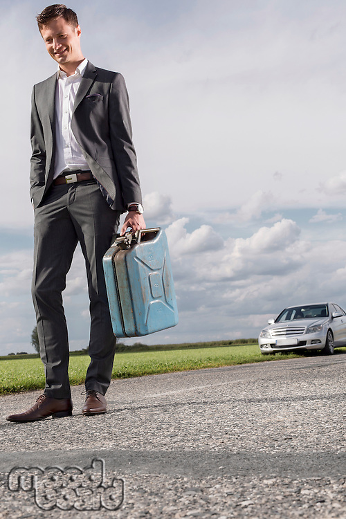 Full length of young businessman carrying gas can with broken down car in background at countryside