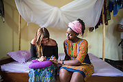 VSO ICS volunteers Francisca Mlingwa and Josie Kearney take some time out to paint their nails in their host home. Volunteers stay with local families get the full experience. Lindi, Lindi region. Tanzania.