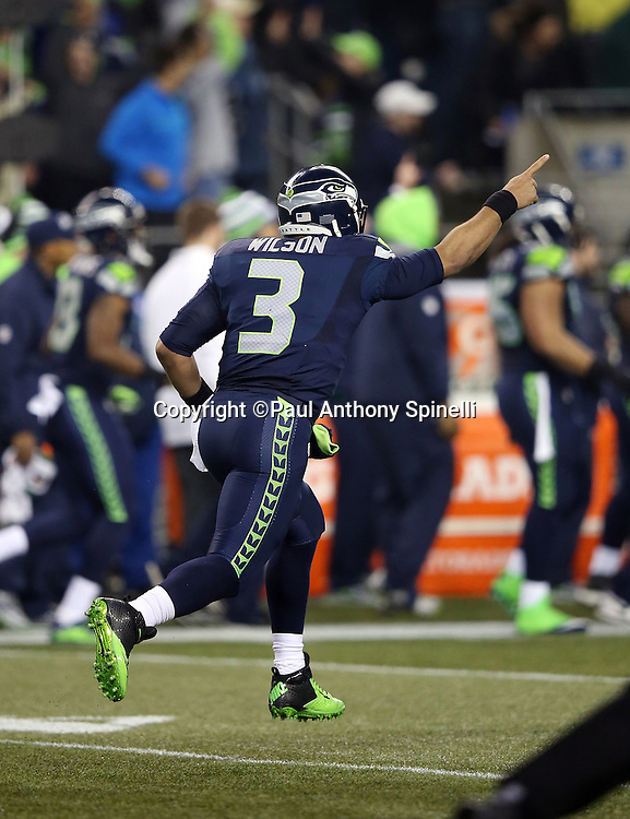 Seattle Seahawks quarterback Russell Wilson (3) points in the air as he runs down field in celebration after throwing a 63 yard touchdown pass for a 14-7 second quarter Seahawks lead during the NFL week 19 NFC Divisional Playoff football game against the Carolina Panthers on Saturday, Jan. 10, 2015 in Seattle. The Seahawks won the game 31-17. ©Paul Anthony Spinelli
