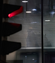 © Licensed to London News Pictures. 23/03/2018. London, UK. An Information Commissioner's Office (ICO) enforcement officer is glimpsed through the blinds inside the London headquarters of data firm Cambridge Analytica. The ICO have just been granted a warrant to allow them to search the office. Cambridge Analytica has been implicated in an investigation into the misuse of Facebook user data to influence the outcome of elections. Photo credit: Ben Cawthra/LNP