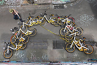 Scott Wilson, a ''bike wrangler'' hired by oBike, dismantles an art installation that was stuck to a brick wall in a lane way in Fitzroy on October 24, 2017 in Melbourne, Australia. The yellow oBikes work on the premise of dockless locking, meaning the bikes can be left anywhere convenient. Since their introduction in June, oBikes have been found stuck up trees, on top of portable toilets and dumped in the Yarra River. Wilson says his picks up to 50 oBikes every day.