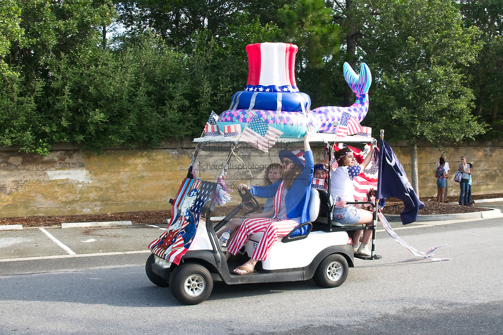 A family rides along in a golf cart decorated in patriotic bunting during the annual Sullivan's Island Independence Day parade July 4, 2017 in Sullivan's Island, South Carolina. The tiny affluent sea island hosts a bicycle and golf cart parade through the historic village.