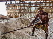 22 FEBRUARY 2017 - BAN LAEM, PETCHABURI, THAILAND: A salt worker works in a warehouse during the salt harvest in Petchaburi province of Thailand, about two hours south of Bangkok on the Gulf of Siam. Salt is collected in coastal flats that are flooded with sea water. The water evaporates and leaves the salt in large pans. Coastal provinces south of Bangkok used to be dotted with salt farms, but industrial development has pushed the salt farms down to remote parts of Petchaburi province. The harvest normally starts in early February and lasts until early May, but this year's harvest was delayed by a couple of weeks because of unseasonable rain in January that flooded many of the salt collection ponds.    PHOTO BY JACK KURTZ